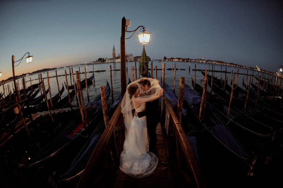 Bride & groom above gondola Venice