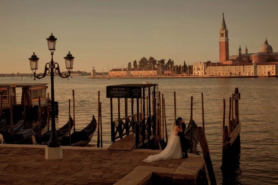 A bride & groom embrace in a deserted landscape near the Gondolas as the sunrise illuminates the Church of San Giorgio Maggiore across the lagoon in Venice Italy. Venice portrait photography by Kurt Vinion.